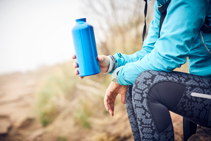 Midsection of traveler holding water bottle. Female is wearing casuals. She is sitting on rock.