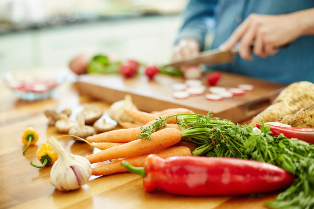 Various vegetables on table with woman chopping radish in backgr