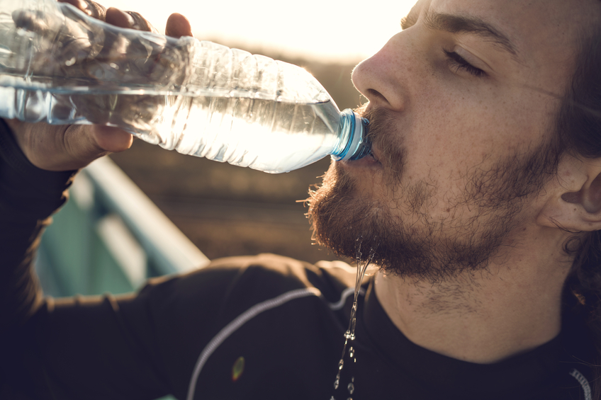Close-up of young man drinking water on the bridge.