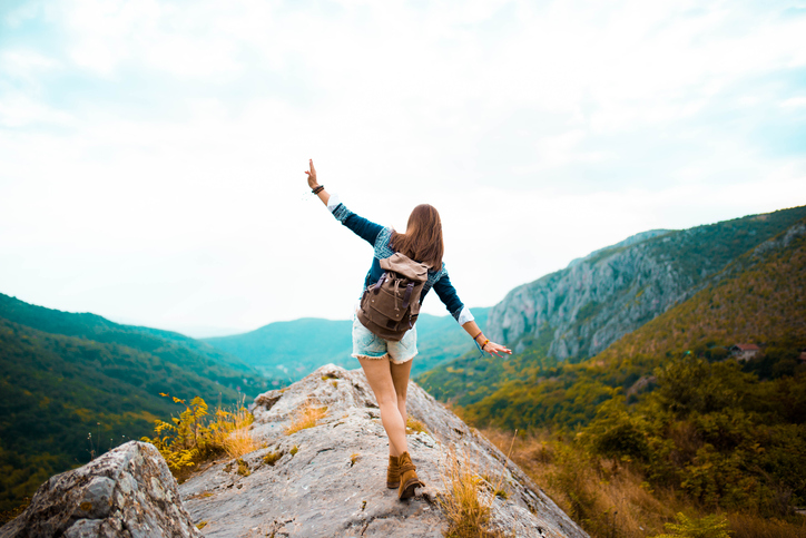 Young Hippie girl taking a walk on top of a mountain and enjoying the day. rear view