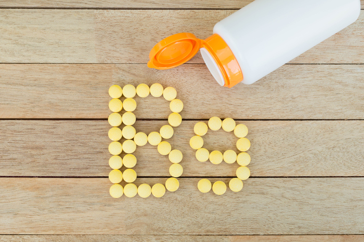 Yellow pills forming shape to B9 alphabet on wood background