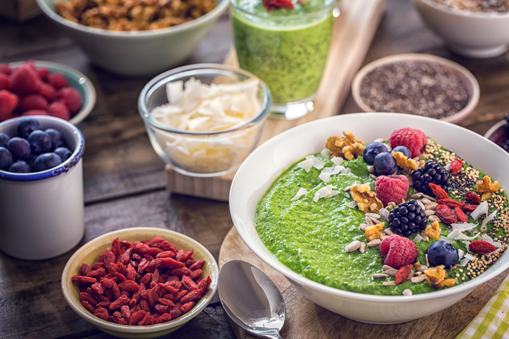 Green breakfast smoothie in bowl with superfoods like chia, quinoa, goji, fresh berries and sunflower seeds.