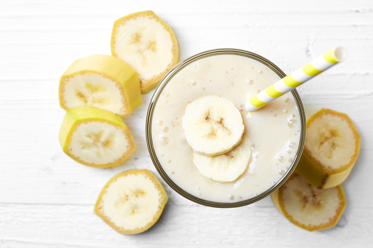Glass of banana smoothie on white wooden background from top view