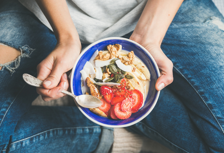 Eating healthy breakfast bowl. Yogurt, granola, seeds, fresh and dry fruits and honey in blue ceramic bowl in woman' s hands. Clean eating, dieting, detox, vegetarian food concept