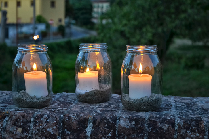 View of glass jars with lit candles inside