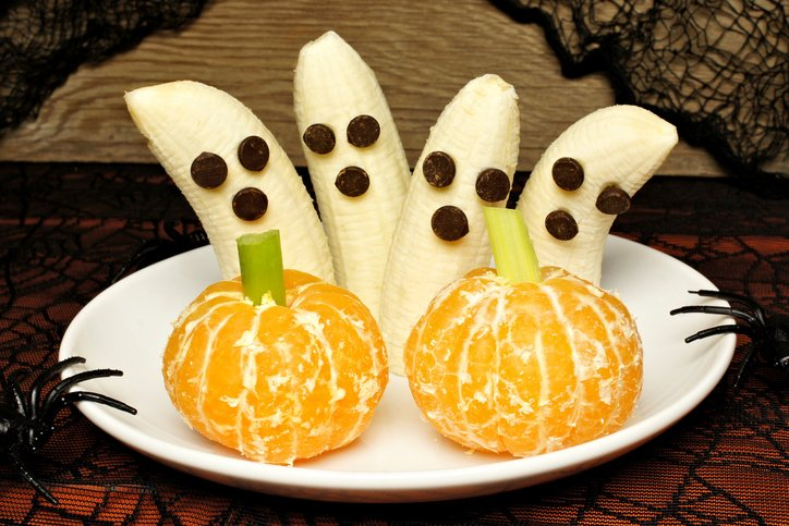 Healthy Halloween treats, banana ghosts and orange pumpkins, on a plate with holiday decor