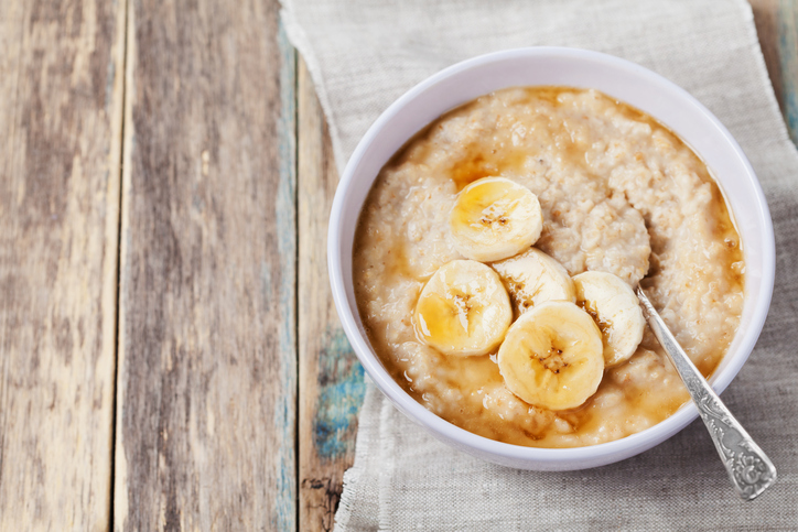 Bowl of oatmeal porridge with banana and caramel sauce on rustic table, hot and healthy breakfast every day, diet food