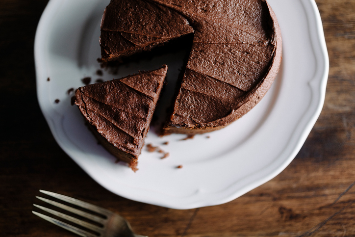Whole sliced Chocolate cake with slice slightly removed. Photographed in window light with Nikon D800+50mm Zeiss Lens at ISO 100. Image Processed from raw file with VSCO Film Kodak Portra film simulation with film grain for a slightly more lo-fi look.