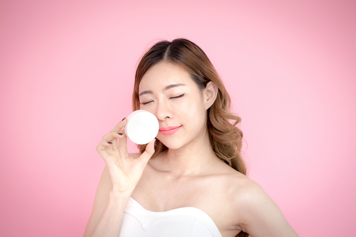 Young beautiful korea woman holding product in hand with relax emotion at pink background, 20-30 year old.