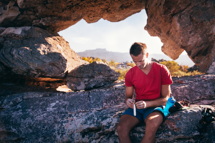Man opens protein bar while sitting on rock. In the background are extreme rock formations where he has been rock climbing.