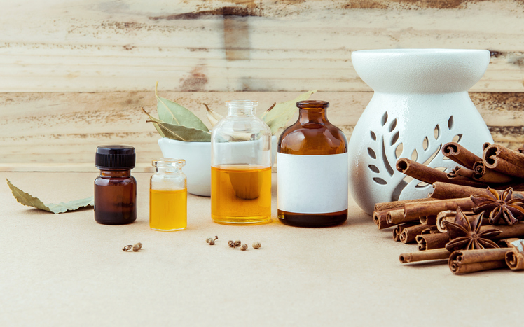 Bottle of essential oil for ayurveda massage with cinnamon stick ,star anise and bay leaves with selective focus on shabby wooden background .